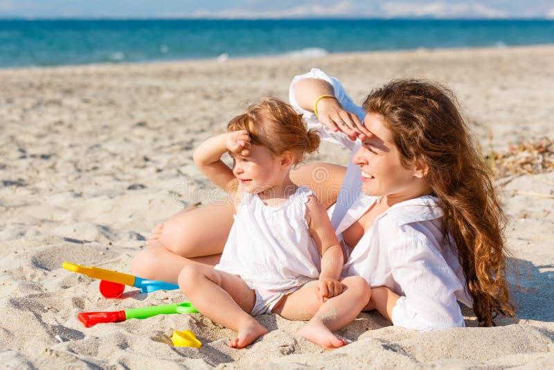 Mère avec le petit descendant sur la plage photos stock