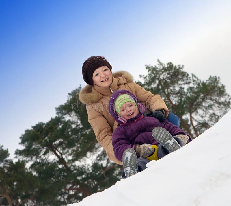Mère avec le petit enfant glissant dans la neige photo libre de droits