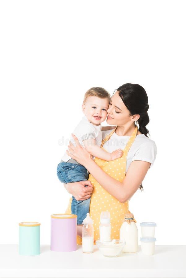 mère avec le petit fils dans des mains à la table avec des enfants nourriture et lait image stock