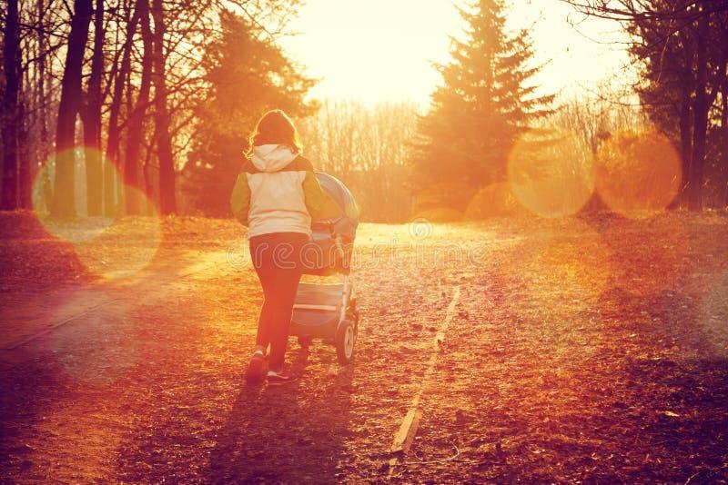 Mère avec le promeneur de bébé marchant en Autumn Park photographie stock libre de droits