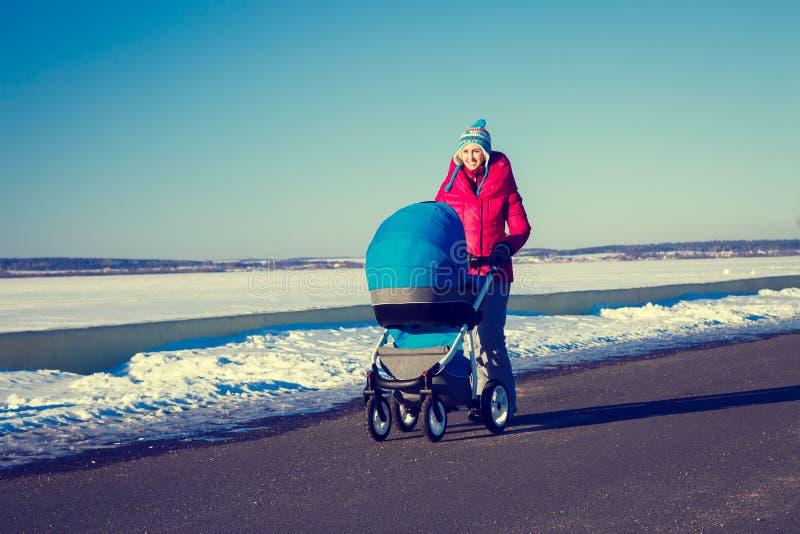 Mère avec le promeneur de bébé marchant en parc d'hiver photo stock