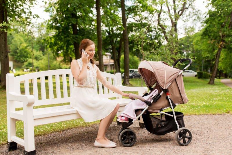 Mère avec le promeneur invitant le smartphone au parc images libres de droits