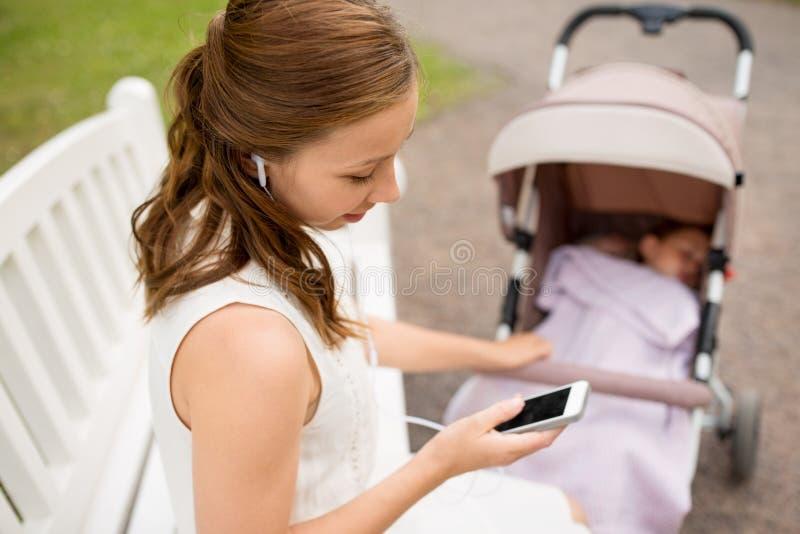 Mère avec le smartphone, les écouteurs et la poussette photos libres de droits