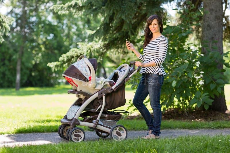 Mère avec le téléphone portable et le chariot marchant dedans image libre de droits
