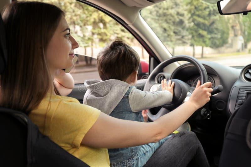 Mère avec peu de fils sur des genoux conduisant la voiture et parlant par le téléphone photo libre de droits