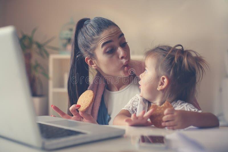 Mère avec sa fille à la maison ayant le petit déjeuner et les valeurs maximales de concentration au poste de travail photo stock
