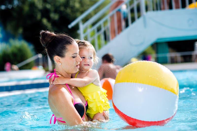 Mère avec sa fille dans la piscine Été ensoleillé photographie stock libre de droits