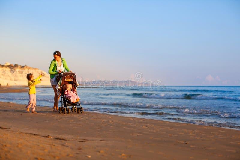 Mère avec sa fille et bébé sur une plage sablonneuse images stock