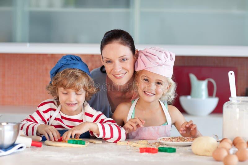 Mère avec ses deux gosses regardant dans la cuisine photo libre de droits