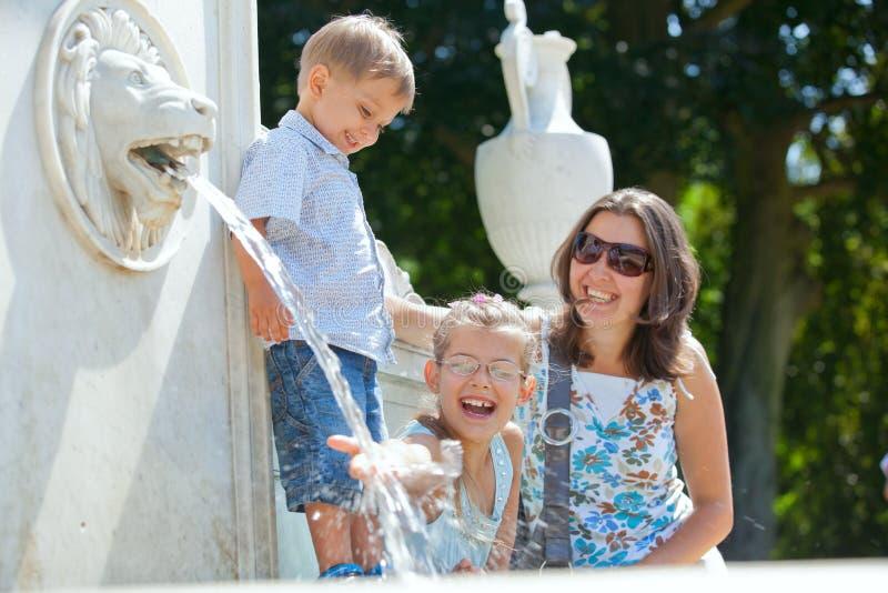 Mère avec ses gosses jouant avec de l'eau photo stock