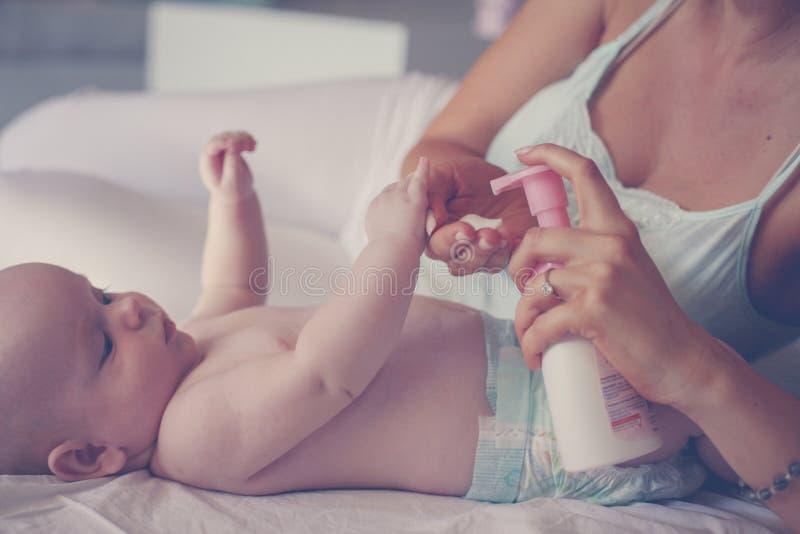 Mère avec son bébé par à la maison La mère emploie une crème corporelle, et p photos stock