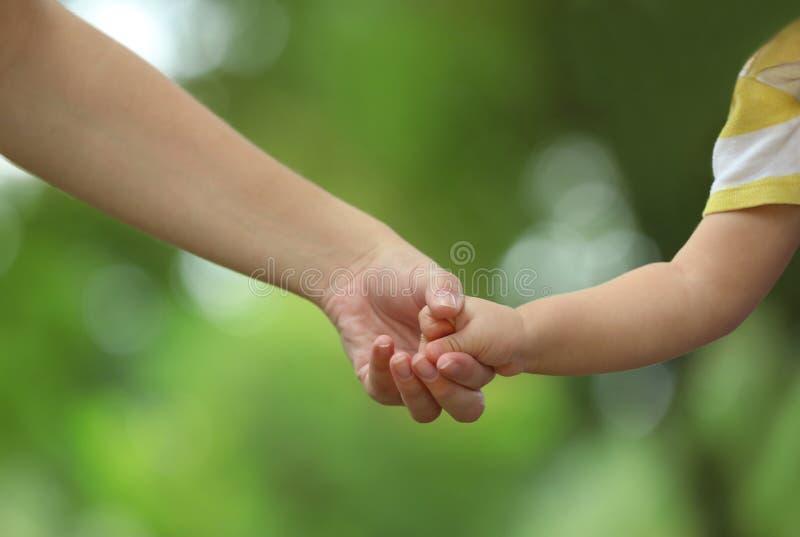 Mère avec son bébé tenant des mains ensemble en parc photo libre de droits