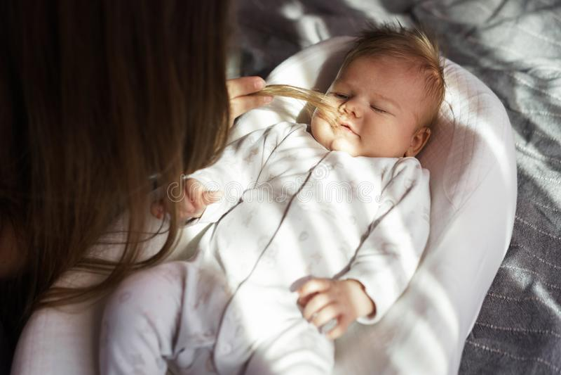 Mère avec son fils nouveau-né sur le lit dans les rayons de la lumière du soleil images stock