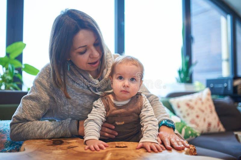 Mère avec un bébé de 1 an s'asseyant sur un sofa à la maison photographie stock libre de droits