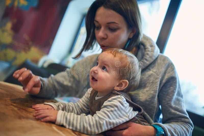 Mère avec un bébé de 1 an s'asseyant sur un sofa à la maison photographie stock