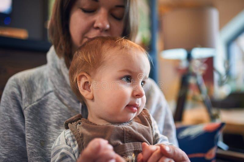 Mère avec un bébé de 1 an s'asseyant sur un sofa à la maison images stock