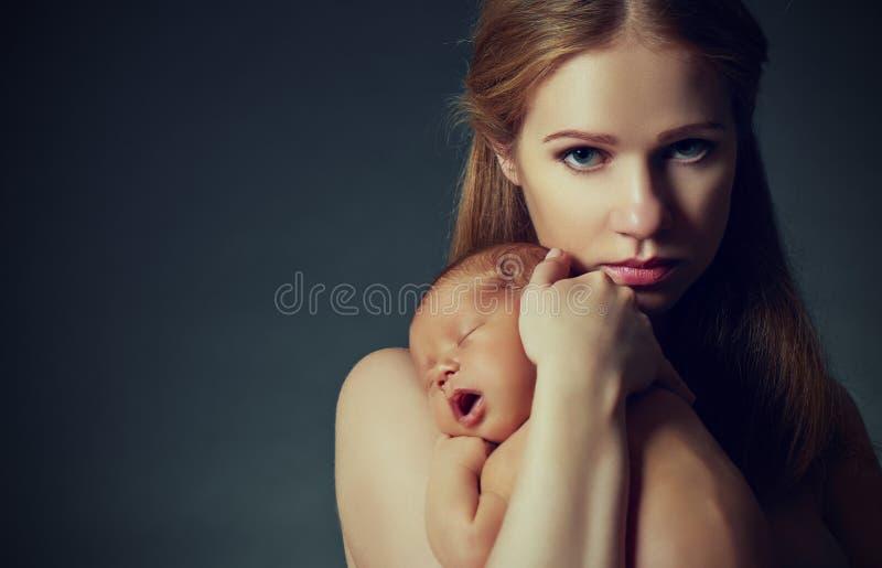 Mère avec un bébé nouveau-né de sommeil sur l'obscurité image stock