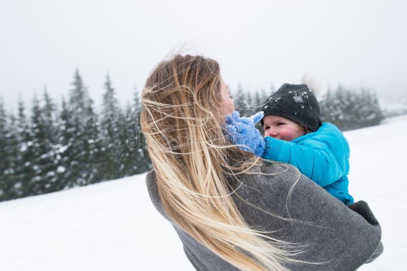 Mère ayant l'amusement avec son fils Nature de l'hiver photographie stock