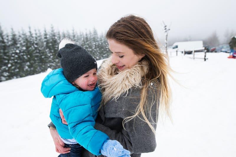 Mère ayant l'amusement avec son fils Nature de l'hiver images stock