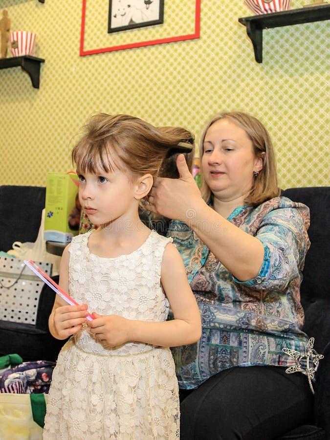 mère balayant sa fille La fille dans une belle robe va à l'anniversaire photographie stock