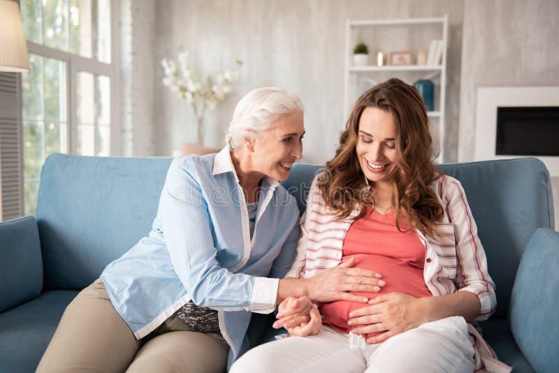 Mère bienfaisante venant pour rendre visite à sa fille enceinte photos stock