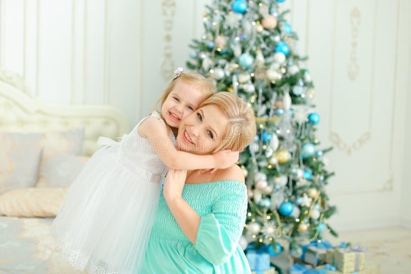 Mère caucasienne portant la robe bleue et étreignant la petite fille près de l'arbre de Noël photo libre de droits