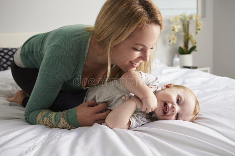 Mère caucasienne se mettant à genoux sur le lit, chatouillant sa fille de bébé images stock