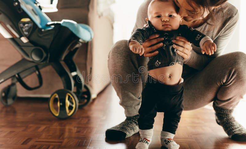 Mère choyant son bébé la tenant image stock