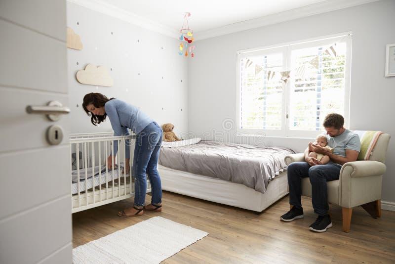 Mère composant le lit dans le berceau de crèche pour le fils nouveau-né image libre de droits