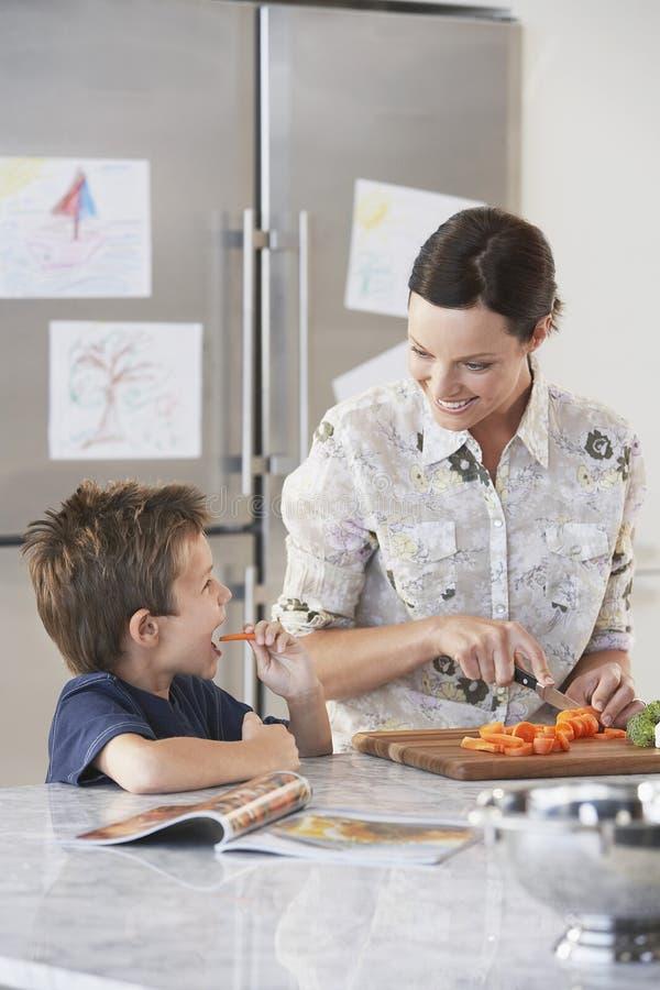 Mère coupant la carotte tandis que fils mangeant à la cuisine photographie stock libre de droits