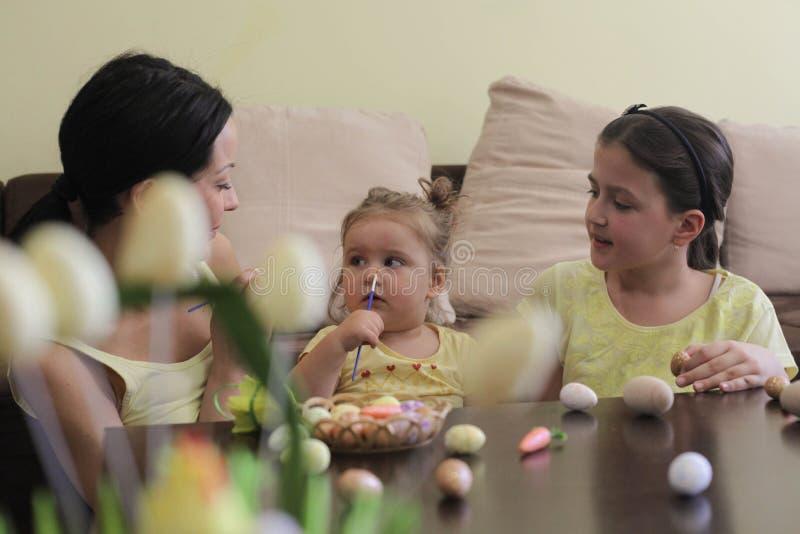 Mère décorant des oeufs avec des filles photos libres de droits
