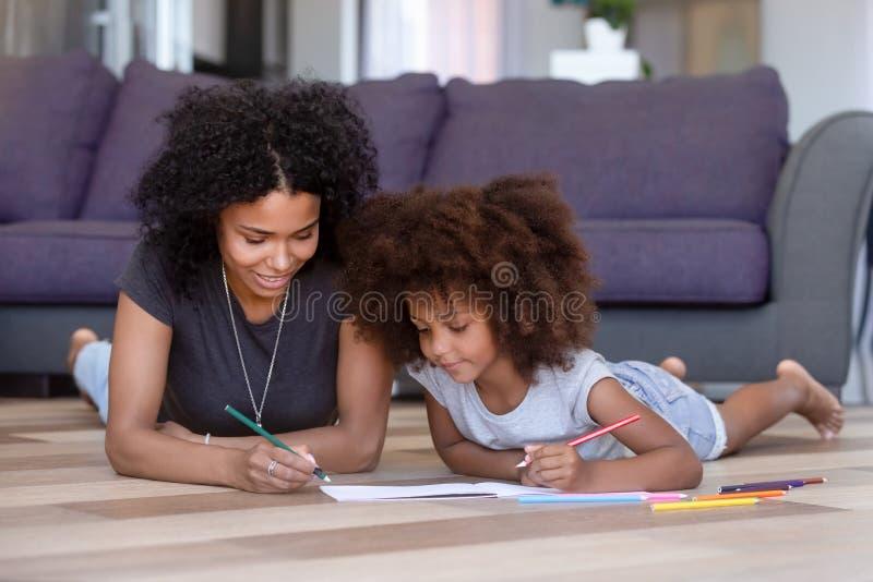 Mère d'afro-américain colorant avec la fille, se trouvant sur le plancher image libre de droits