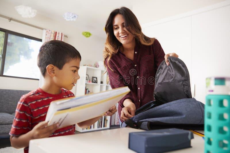 Mère dans le fils de aide de chambre à coucher pour emballer le sac prêt pour l'école image libre de droits