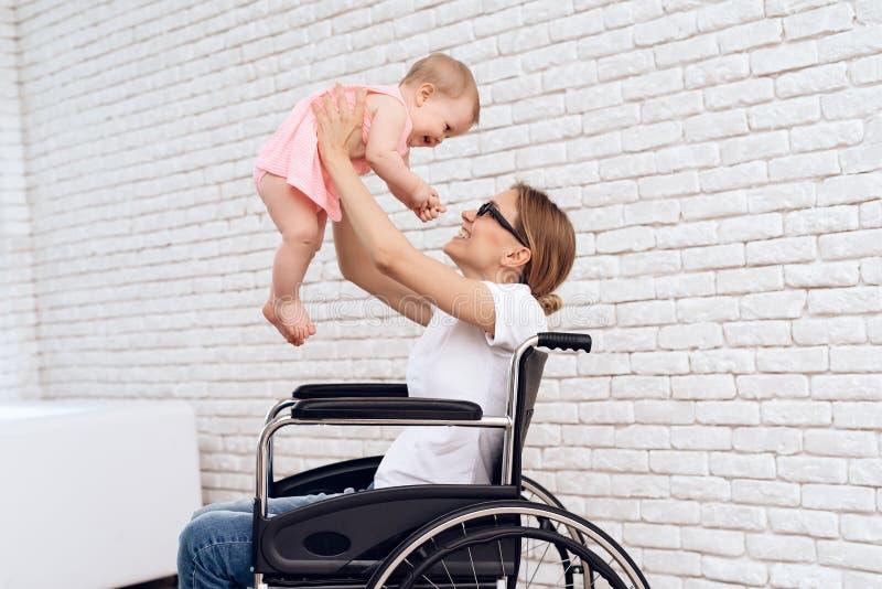 Mère dans le jeu de fauteuil roulant avec le bébé nouveau-né photos libres de droits