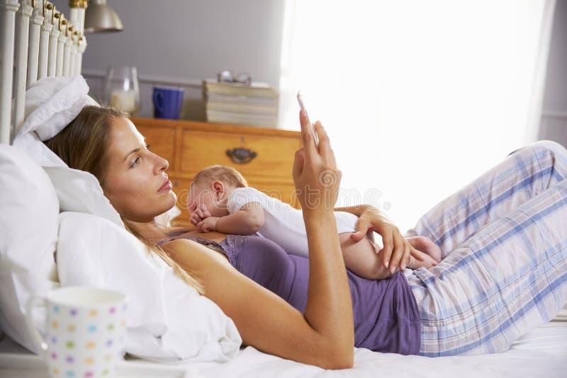 Mère dans le lit avec la fille de bébé vérifiant le téléphone portable image stock