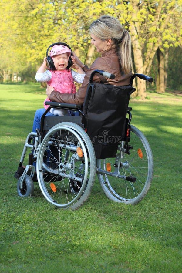 Mère dans un fauteuil roulant avec le bébé sur son recouvrement photo stock