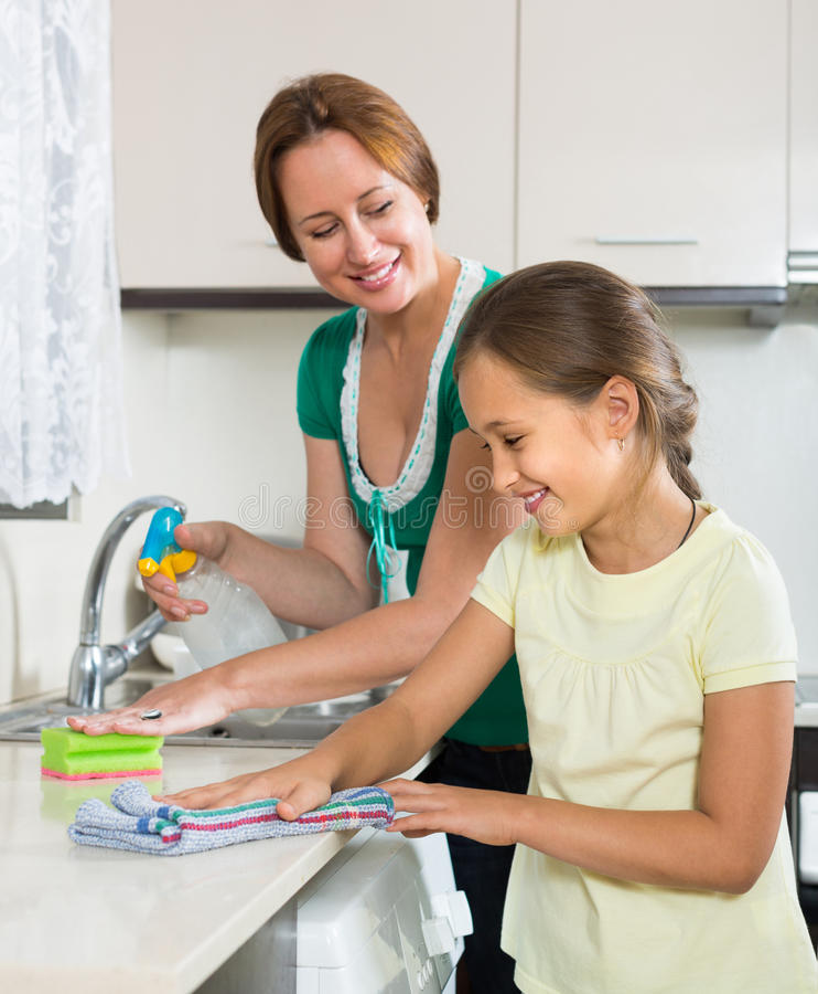 Mère de aide de petite fille à la cuisine image stock