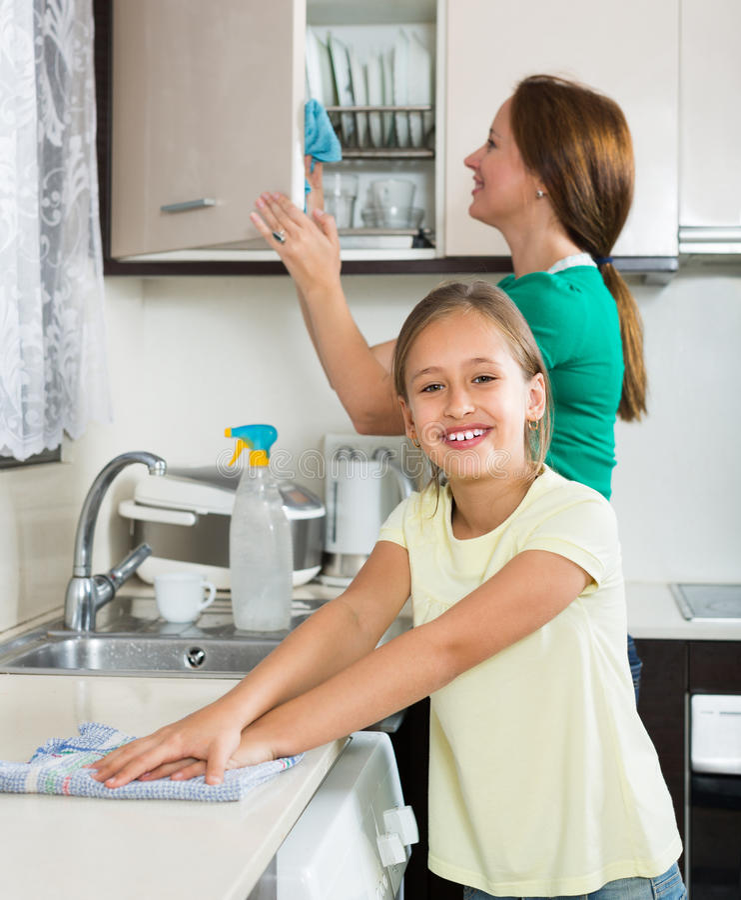 Mère de aide de petite fille à la cuisine photo stock