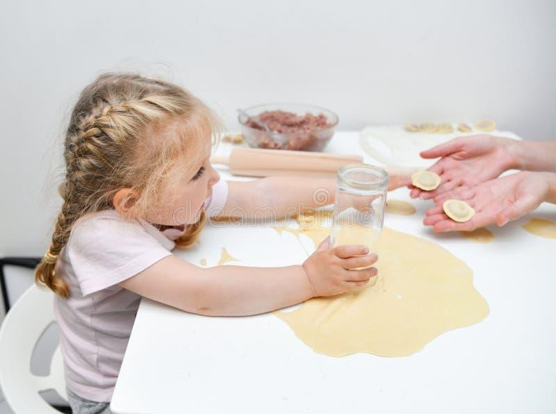 Mère de aide de fille pour faire des boulettes photographie stock