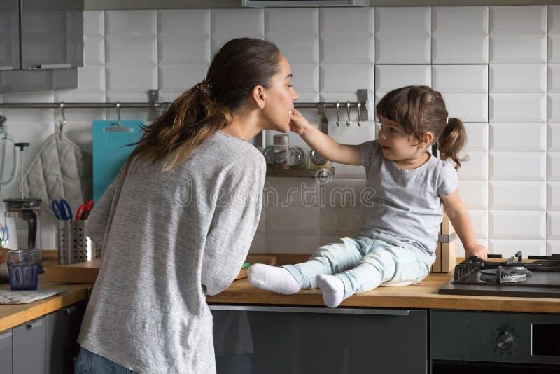 Mère de alimentation de petite fille ayant l'amusement dans la cuisine à la maison image stock