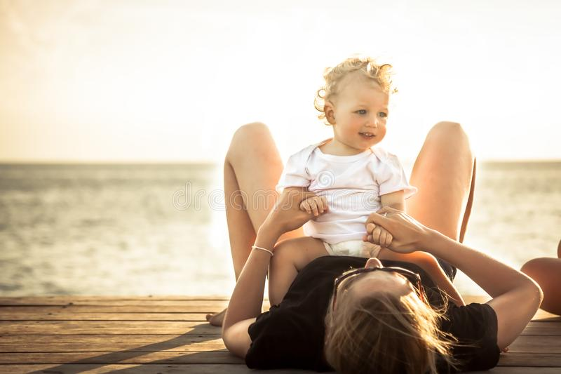 Mère de bébé d'enfant détendant ensemble la plage pendant la lumière du soleil de vacances de plage d'été image libre de droits