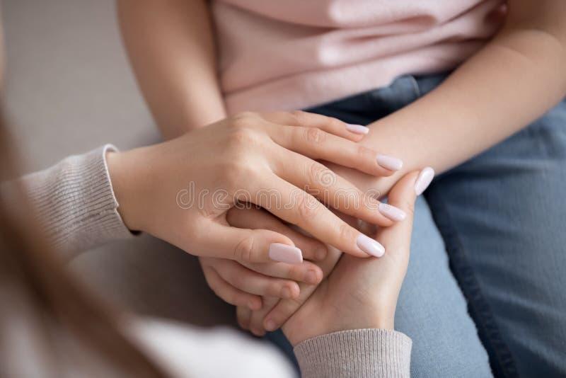 Mère de femme adulte tenant des mains d'enfant, confiance de famille, plan rapproché photos stock
