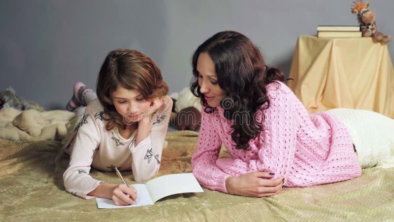Mère de soin aidant sa jeune fille à écrire la lettre de salutation à Santa Claus images libres de droits