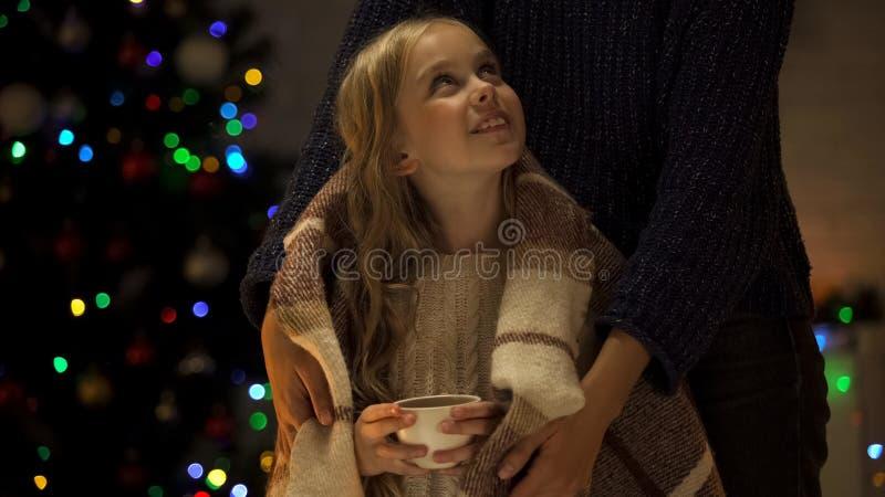 Mère de soin couvrant la tasse mignonne de participation de fille de cacao de plaid, temps de Noël image stock