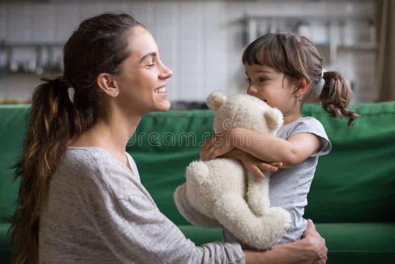 Mère de sourire étreignant la fille mignonne montrant l'amour et le soin image stock