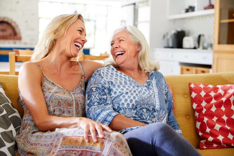 Mère de sourire avec la fille adulte détendant sur Sofa At Home photos stock