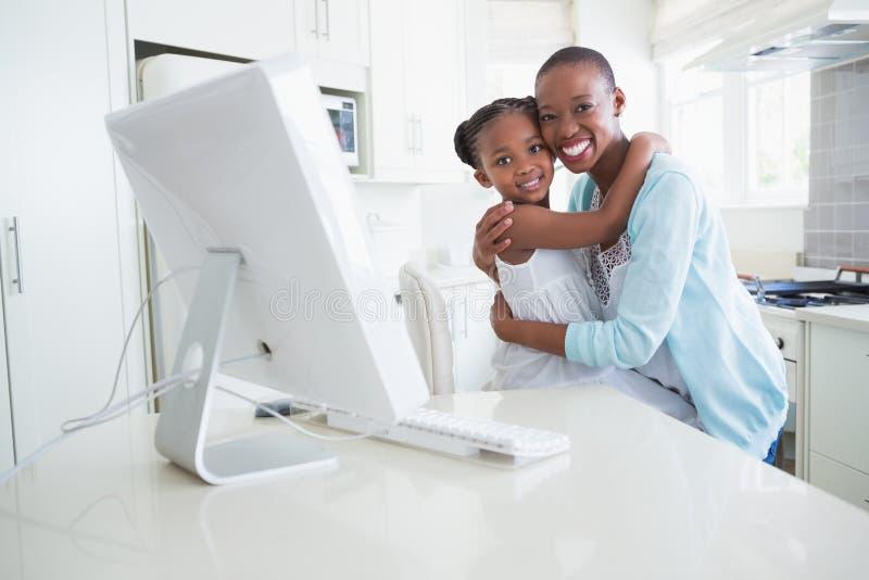 Download Mère De Sourire Heureuse Avec Sa Fille à L'aide De L'ordinateur Photo stock - Image du durée, vêtement: 56484456