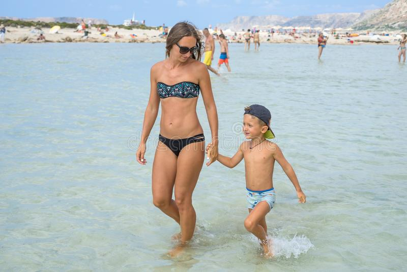 Mère de sourire heureuse et son fils jouant et courant sur la plage Concept de famille amicale Jours d'été heureux Lagune de Balo photos stock