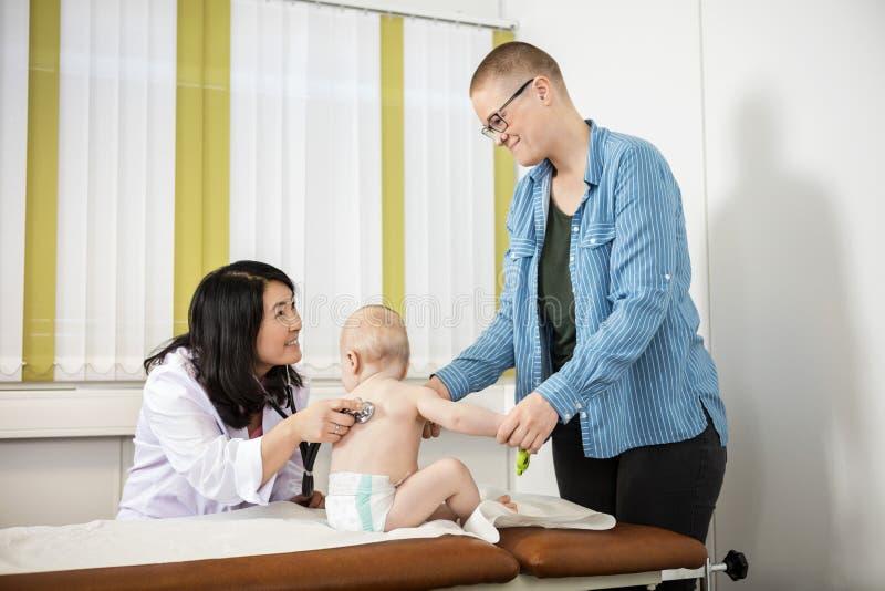 Mère de sourire regardant le lit d'Examining Baby On de pédiatre photo stock