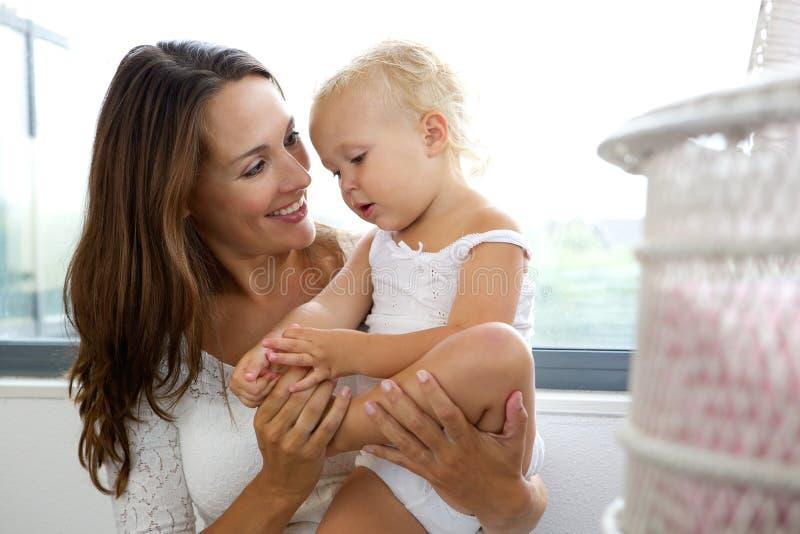 Mère de sourire s'occupant de sa fille images libres de droits